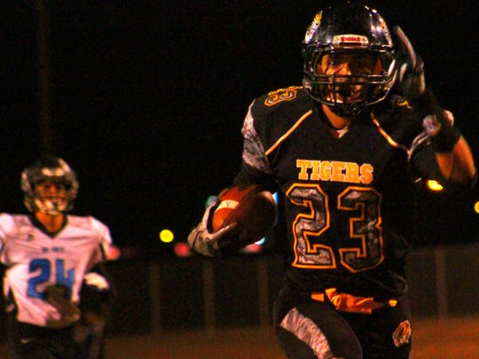 Alamogordo's David Johnson, right, holds up the number one as he walks into the end zone Friday night.