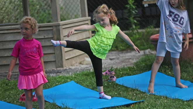 Practicing yoga at University of Delaware's Laboratory Preschool are, from left, Mariska Frankfort, Taylor Wright and Lily Bielek. They're taking part in Mindfulness Camp.