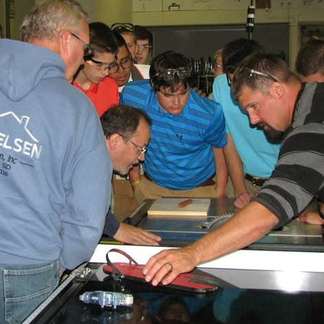 Member of the Home Builders Association of the Sioux Empire and students at O'Gorman High School examine a table saw donated by HBASE's charitable arm.