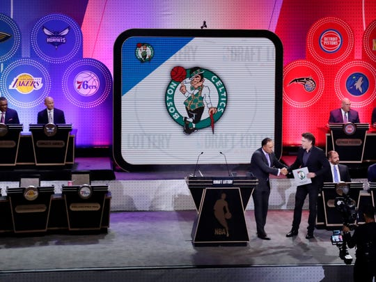 NBA Deputy Commissioner Mark Tatum, front left, shakes hands with Boston Celtics co-owner Wyc Grousbeck, right, after the Celtics won the first pick at the NBA basketball draft lottery Tuesday, May 16, 2017, in New York.