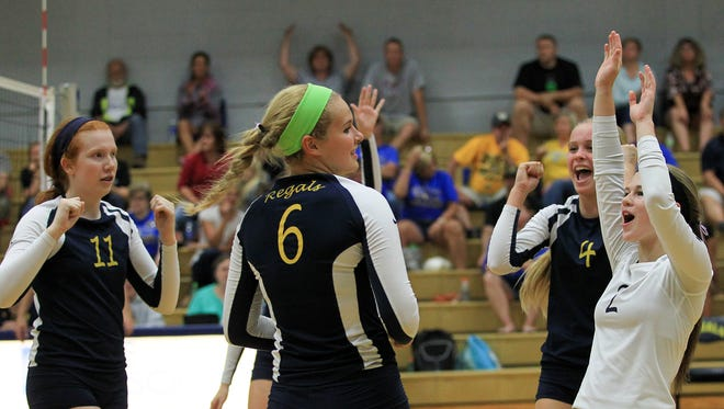 Regina teammates celebrate a point during their game against Wilton on Tuesday, Sept. 15, 2015.