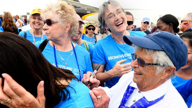 Secretary of the Air Force Heather Wilson laughs with Women's Auxiliary Service Pilot Jane Doyle while she autographs a T-shirt following a group portrait of women aviators in Oshkosh, Wisc., July 26, 2017.
