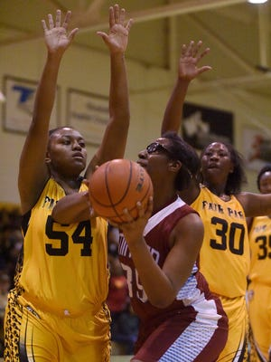 Minden's Derica Gilbert goes up for a shot during a game against Fair Park's Savannah Thomas (54) and Dominique Johnson (30).