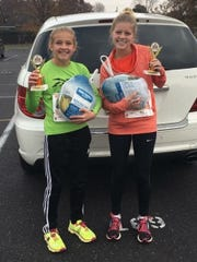 Chambersburg's Camryn Kiser, 12, left, and sister Cadie, 17, each won their respective age groups at last week's Greencastle Turkey Trot.