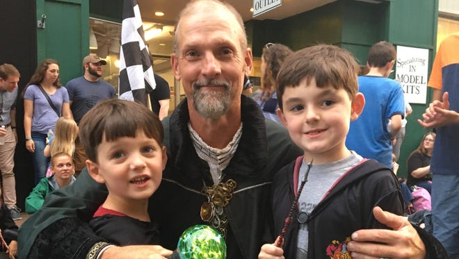 Wearing their Hogwarts robes, Emerson and Wesley Thomas, of Midloathian, stand next to Staunton's Dan Pittman who is Hogwarts Founder Salazar Slytherin during Queen City Mischief & Magic on Friday, Sept. 22, 2017.