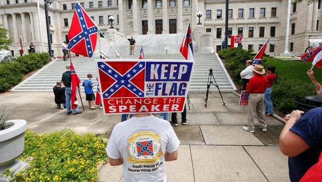 "In this July 6 photograph, a small group of Mississippi and Confederate flag-waving citizens participate in a rally sponsored by the Magnolia State Heritage Campaign seeking publicity and support to help keep the Confederate battle emblem in the Mississippi flag on the steps of the Capitol in Jackson, Miss. House Speaker Philip Gunn said his own faith causes him to see the Mississippi flag as ""a point of offense that needs to be removed."" Several cities and counties, and two universities stopped flying the state flag. Republican Gov. Phil Bryant says he respects results of a 2001 election, when voters chose to keep the Confederate emblem on the flag. However he also said if the issue is going to be revisited, it should happen during the November 2016 election."