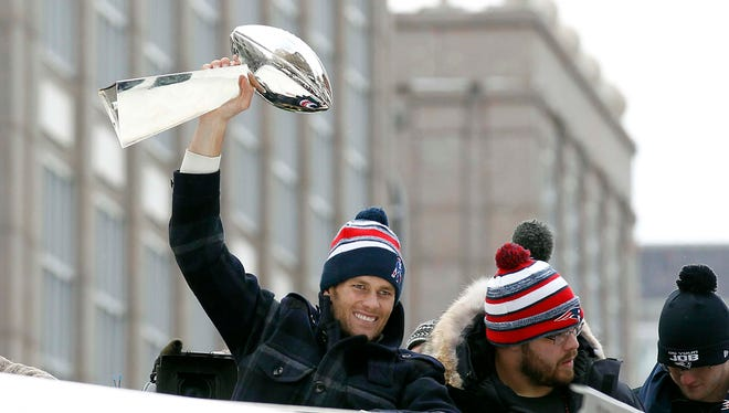 New England Patriots quarterback Tom Brady holds up the Vince Lombardi Trophy during the Super Bowl XLIX victory parade.