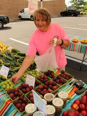 Melissa Knight prepares to close her booth Saturday after selling out most of her fruit and vegetables at the Farmers Market at the Shoppes at EastChase. Alvin Benn/Special to the Advertiser.