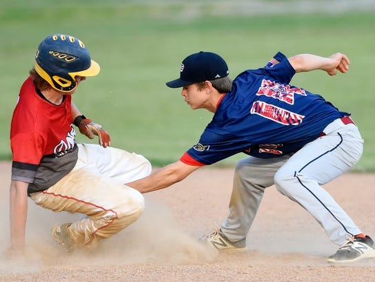 Dover's Anthony Friday, left, avoids a tag by Pleasureville's