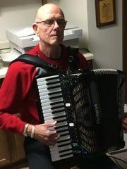 Mike DeSciscio plays his accordion in his office/practice