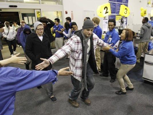 Employees greet Black Friday shoppers at Best Buy. (AP Photo/Tony Dejak)