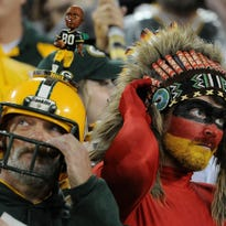 A Packers and Chiefs fan put their headgear back on following the playing of the national anthem.