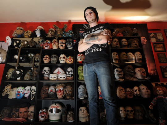 A.J. Good stands with some of the hundreds of masks he's collected since he was six years old.