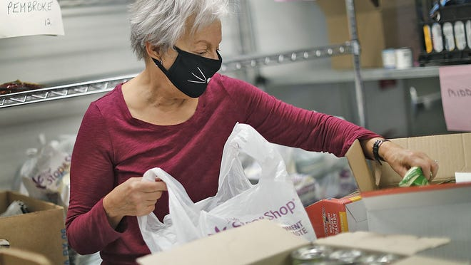 Grace Mahoney, of Plymouth, has volunteered once a week for three years at South Shore Community Action Council in Plymouth, bags food for seniors in the large pantry on Wednesday, Oct. 7, 2020.  Greg Derr/The Patriot Ledger