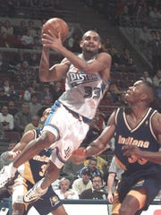 The Pistons' Grant Hill looks to shoot past the Pacers' Antonio Davis.