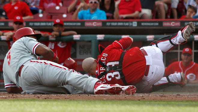Philadelphia Phillies right fielder Marlon Byrd (3) is tagged out at home plate by Cincinnati Reds catcher Devin Mesoraco (39) during the sixth inning at Great American Ball Park.