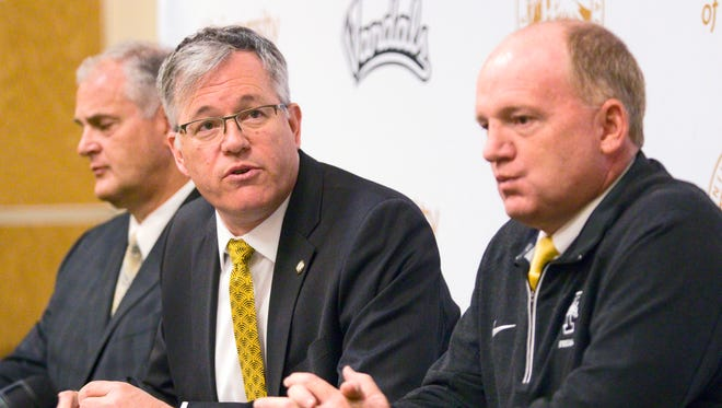 University of Idaho President Chuck Staben, center, athletic director Rob Spear, left, and head football coach Paul Petrino answer questions during a news conference on Thursday, April 28, 2016, at the Kibbie Dome in Moscow, Idaho. Idaho will drop to the Football Championship Subdivision beginning in 2018 and intends to join the Big Sky Conference, school President Chuck Staben said Thursday. (Geoff Crimmins/The Moscow-Pullman Daily News via AP) MANDATORY CREDIT