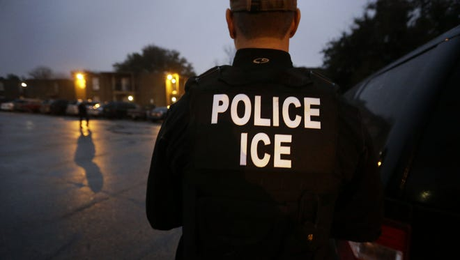 In this March 6, 2015, file photo, U.S. Immigration and Customs Enforcement agents enter an apartment complex looking for a specific undocumented immigrant convicted of a felony during an early morning operation in Dallas.