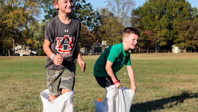 Best friends Alex Judd, left, and Aiden Stone battle it out in a sack race. The boys are first-graders at Reeves-Rogers Elementary. St. Mark's United Methodist Church partners with Reeves-Rogers Elementary for inaugural fall fest.