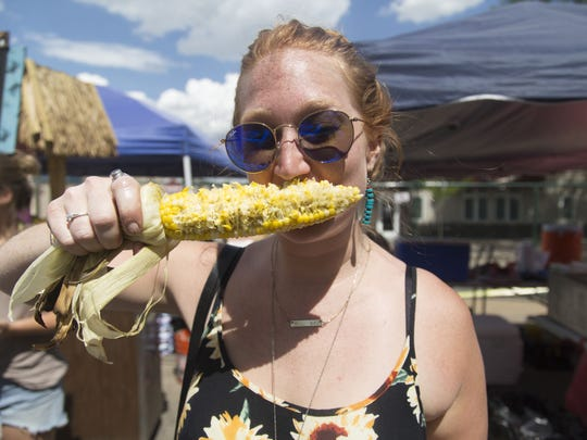 Monica Peterson bites into her corn of the cob at  the 2016 Taste of Fort Collins.