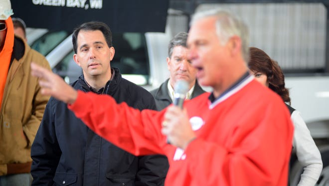 Wisconsin Gov. Scott Walker, left,  listens as Sen. Ron Johnson talks about Walker's record as governor during a campaign visit to Astro Industries in Ashwaubenon October 30, 2014.