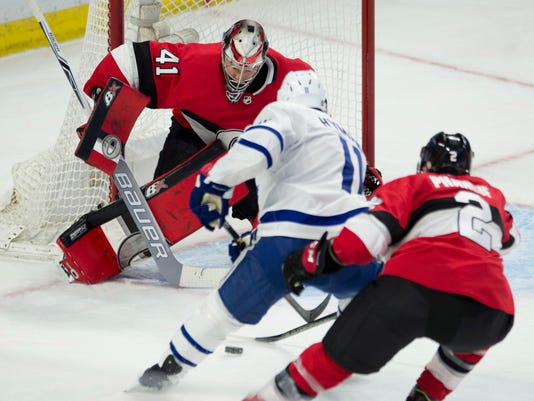 Toronto Maple Leafs center Zach Hyman tries to put the puck past Ottawa Senators goaltender Craig Anderson as he is pressured by defenseman Dion Phaneuf during the second period of an NHL hockey game Saturday, Jan. 20, 2018, in Ottawa, Ontario. (Adrian Wyld/The Canadian Press via AP)