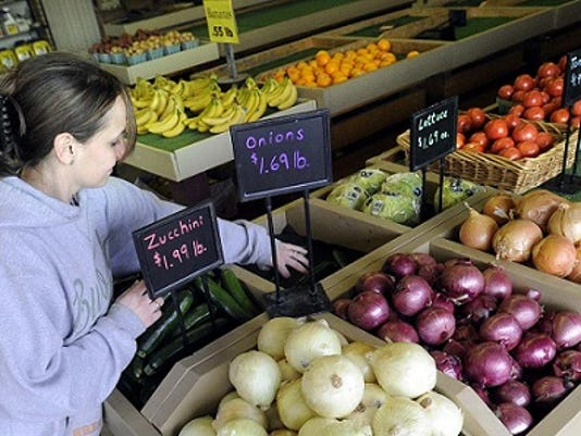 YDR photo; Shauna Thomas, an employee at Whitecomb's Produce, sets up the signs at the stand as the store opened for the season March 11.