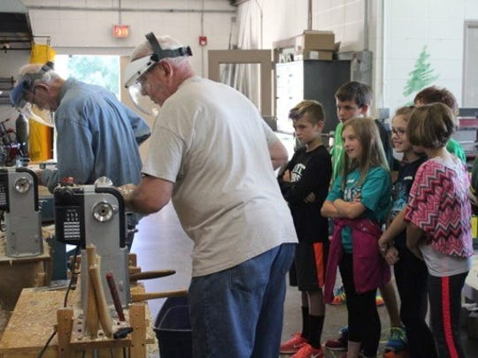 Students watch as woodturners use lathes to handcraft