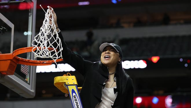 South Carolina  head coach Dawn Staley celebrates with the net after winning the women's national championship.