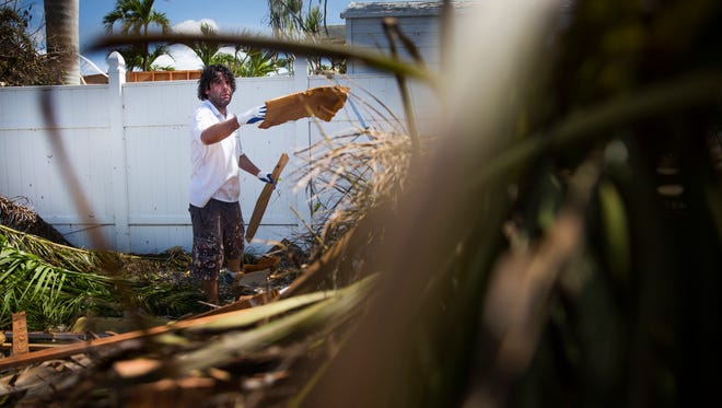 Kristian Schomburg throws debris into a pile while cleaning up at the Snook Inn in Marco Island on Tuesday, September 12, 2017, two days after Hurricane Irma.