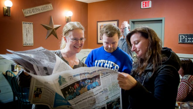 Tabita Green, Geoffrey Dyck and Emily Neal look at a newspaper in Decorah on March 22.