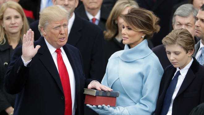 U.S. President Donald Trump takes the oath of office as his wife Melania Trump holds the bible and his son Barron Trump looks on, on the West Front of the U.S. Capitol on January 20, 2017 in Washington, DC.