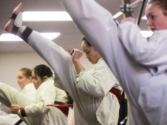 Shania Van Spyk, 13, practices kicks with classmates