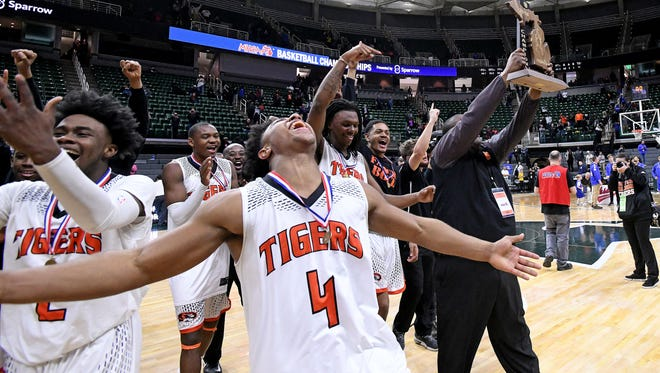 Benton Harbor's Dennie Brown (4) and the rest of the team celebrate as Benton Harbor beats Grand Rapids Central Christian, 65-64 in overtime in its  Class B championship game.