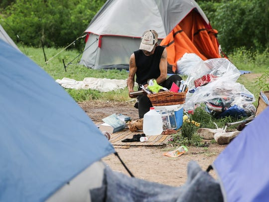 Reggie Felton cleans up objects from an abandoned tent in the tent city under Houston Harte Expressway on April 10, 2017.