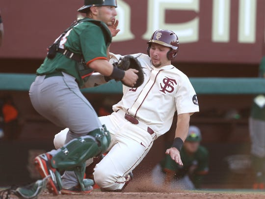 FSU's Cal Raleigh slides in safely at home plate for a run past Miami's Michel Amditis during their game at Dick Howser Stadium in Tallahassee, Florida, on Saturday, April 28, 2018.
