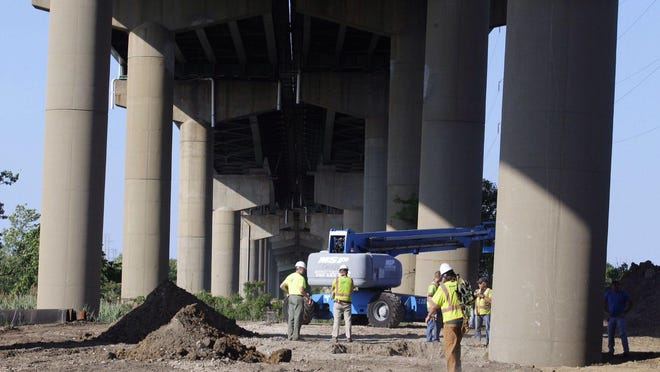 DelDOT crew members surround a support column holding a span of the I-495 bridge over the Christina River in Wilmington after it shifted, prompting the closure of the interstate on Monday.