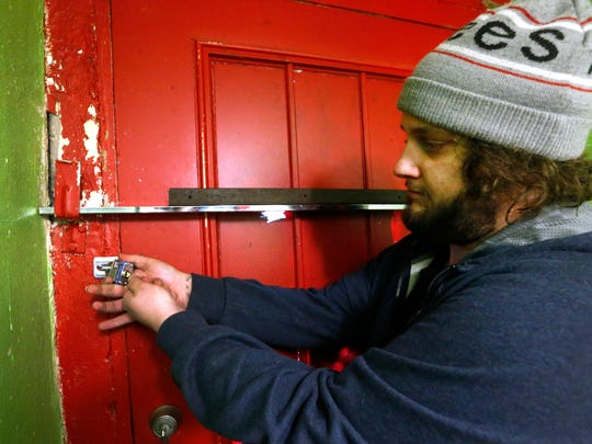"Marshall Pointer, an employee of Enchanted Planet removes the padlock from the back door of the store after Judge Royce Taylor allowed stores that were padlocked by authorities to be reopened after they were closed following the ""Operation Candy Crush"" CBD raids earlier this month, following the arraignments on Friday Feb. 16, 2018."