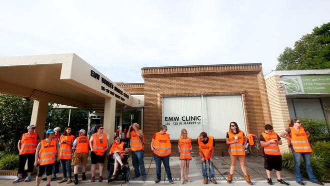 Volunteers  lineup outside  to help clients enter the EMW Women's Surgical Center on Saturday morning.