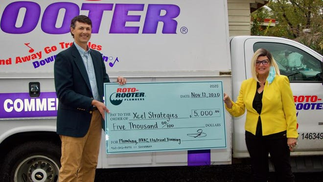 Jay Thompson accepts $5,000 from Sherry Daniel to fund a mobile trailer that will provide plumbing, HVAC and electrical training opportunities to young men between the ages of 15 and 25.