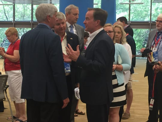 Michigan Gov. Rick Snyder, left, meets up with Attorney General Bill Schuette at a reception for Michigan delegates at the GOP convention in Cleveland on Thursday, July 21, 2016.