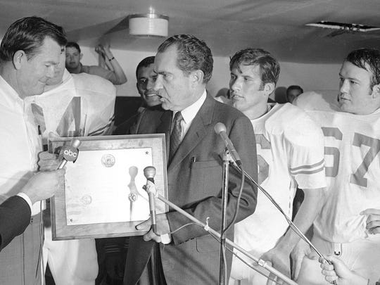 FILE - In this Dec. 6, 1969, file photo, President Richard Nixon presents a plaque to Texas football coach Darrell Royal, proclaiming the Longhorns the No. 1 college football team in college football's 100th year, after their 15-14 win over Arkansas in Fayetteville, Ark.  (AP Photo/File)