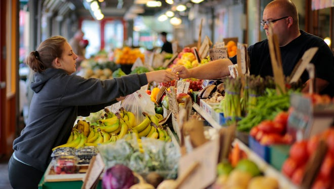 Jaicey Nunley, 20, of Alexandria, Ky., reaches to pick up her produce, Wednesday, Oct. 5, 2016, at Findlay Market in Over-the-Rhine. The market was recently name one of five Great Public Spaces by the American Planning Association.