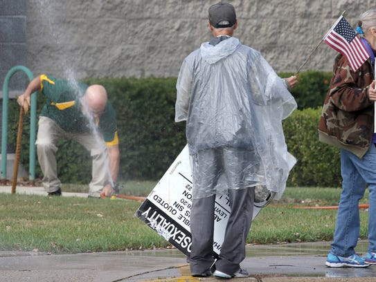 "A West Allis store owner turned on his lawn sprinkler as three people protest outside the Highway 100 store about athletes' unwillingness to show respect for country, flag and president, and targeted consumers purchase of sports merchandise. The sign that protester Colon Hudson is carrying has a message about homosexuality. Protest organizer Bob Braun said a woman gave him the sign years ago and he has carried it in many protests with the message on the front of the sign that says ""Shame."" ""It applies to every protest,"" Braun said."
