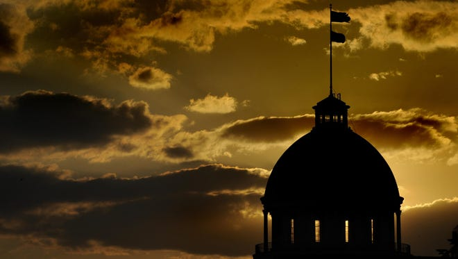 The sun sets behind the state Capitol dome in Montgomery.