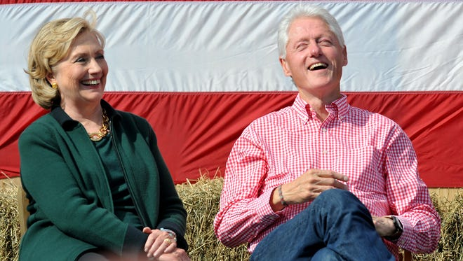 Former President Bill Clinton and his wife former Secretary of State Hillary Rodham Clinton laugh during a speech by U.S. Sen. Tom Harkin (D-IA) during the 37th Harkin Steak Fry, September 14, 2014 in Indianola, Iowa.