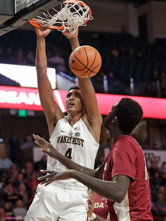 Wake Forest's Doral Moore (4) dunks over Florida State's Christ Koumadje during the first half of an NCAA college basketball game in Winston-Salem, N.C., Wednesday, Jan. 31, 2018. (AP Photo/Chuck Burton)