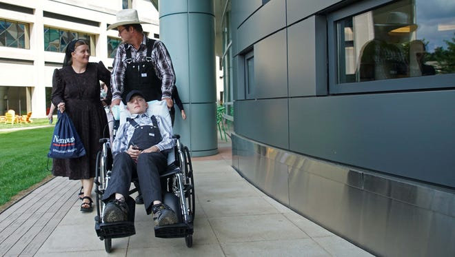 Helena and Gerhard Friessen Fehr, push their 15 year-old son Gerhard is a wheelchair, who is recovering from spine surgery at Nemours/A.I. duPont Hospital for Children Hospital.