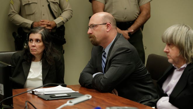 From left Louise Turpin and David Turpin, at far right, are arraigned at the Robert Presley Hall of Justice courthouse in Riverside County on January 18, 2018. At center is Jeff Moore, lawyer for Louise Turpin. The Turpin couple are being charged with child endangerment and torturing their children. In this photo Louise Turpin speaks to her counsel Jeff Moore.