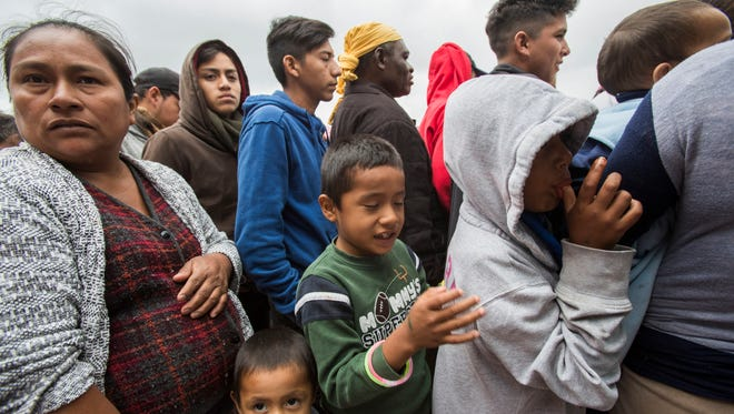 "Central American migrants line up to get food at their encampment at the entrance of the ""El Chaparral' U.S. point of entry in Tijuana, Mexico on May 1, 2018."